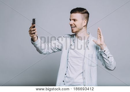 Young cute guy is chatting with his friends through mobile phone and waving them. Delighted man having skype conversation. Close up. Isolated