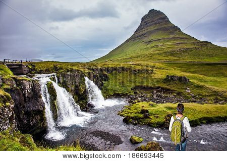 Elderly woman -  traveler with a large backpack admiring the powerful jets of the waterfall Kirkjoufellfoss. Concept of exotic and extreme tourism. Summer in Iceland