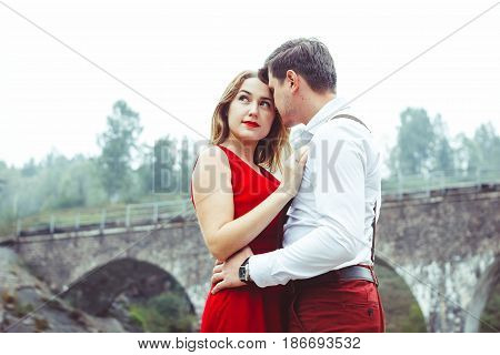 Lovers are standing at the bridge looking at each other