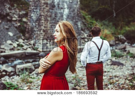 Couple standing in the nature, the girl in front