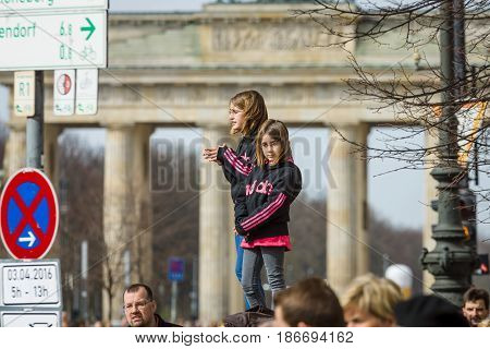 BERLIN - APRIL 03 2016: The annual Berlin Half Marathon. Two girls watching a marathon against the backdrop of the Brandenburg Gate.