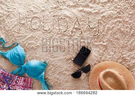 The word Holiday written in a sandy tropical beach