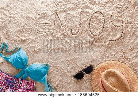 The word Enjoy written in a sandy tropical beach