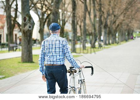 Handsome senior man in blue checked shirt with bicycle in town. Sunny spring day. Rear view.
