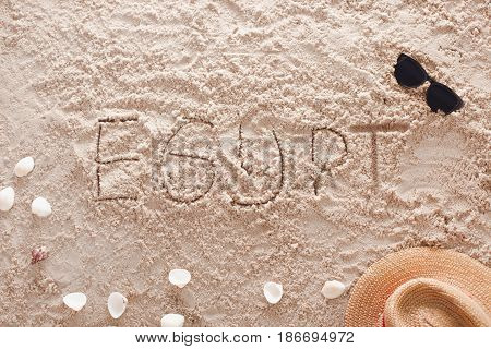 The word Egypt written in a sandy tropical beach