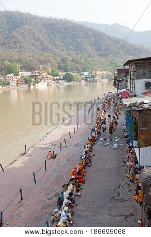 INDIA, LAXMAN JHULA - APRIL 24, 2017: Sadhus waiting for food at the river Ganges in Laxman Jhula on 24th april 2017