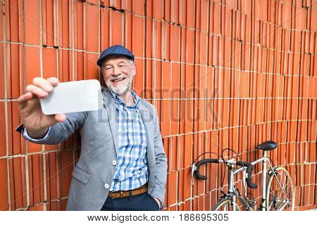 Handsome senior man in blue checked shirt and gray jacket with bicycle holding smart phone, taking selfie. Orange brick wall background.