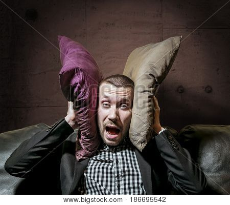 A man in a business suit covering her ears with pillows and screaming from the nerves