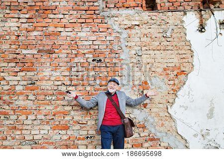 Handsome senior man in gray jacket holding smart phone. Orange brick wall background.