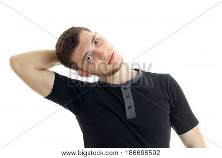 young handsome guy in a black t-shirt holds a hand near his head and posing for the camera isolated on white background