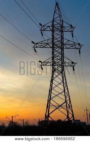Power transmission lines in the background of a sunset and the outlines of the city