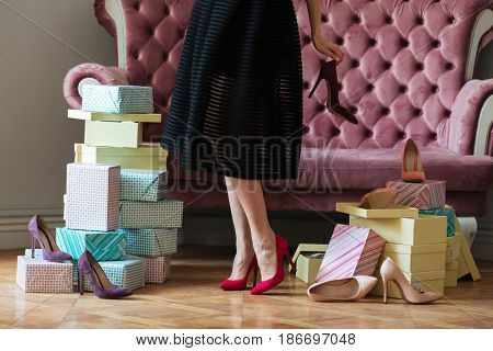 Cropped picture of young lady standing near sofa indoors choosing shoes.