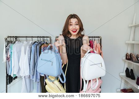 Image of young woman standing in clothes shop indoors choosing between two backpacks. Looking at camera.