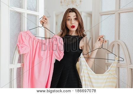 Picture of young woman standing in clothes shop indoors choosing between two dresses. Looking at camera.