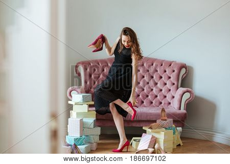 Picture of happy young lady standing near sofa indoors choosing shoes. Looking aside.