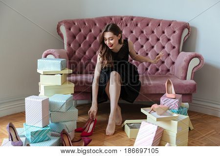 Image of happy young lady sitting on sofa indoors choosing shoes. Looking aside.
