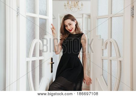 Picture of young happy woman standing in clothes shop indoors. Looking at camera.