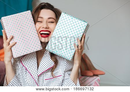 Image of happy young lady indoors with gift boxes. Looking at camera.