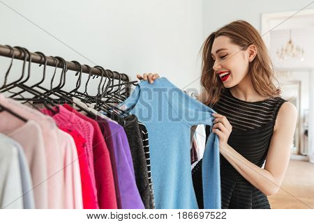 Image of young pretty woman standing in shop indoors choosing clothes. Looking aside.