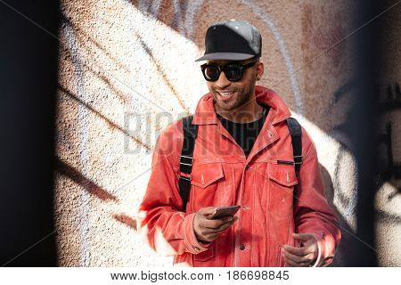 Portrait of a smiling stylish afro american man in sunglasses listening music with mobile phone and earphones while walking in a street