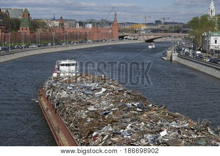Moscow, Russia - May, 7, 2017: The barge is carrying construction debris along the Moscow River opposite the Moscow Kremlin