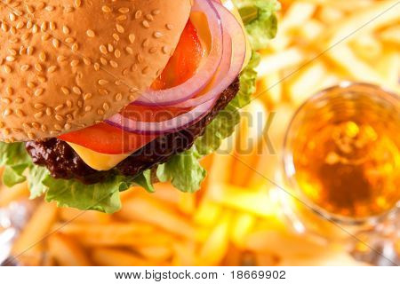 classic beef cheeseburger with potato fries and beer on background, shallow dof
