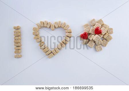 Brown sugar cubes arranged as I love sugar concept