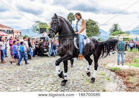 San Juan del Obispo, Guatemala - June 12 2016: Horseback cowgirl rides in horse street parade in village near Antigua, Guatemala