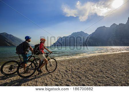 Mountain biking, couple with bikes on Lake Garda, Riva del Garda, Italy