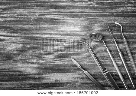 Set of dentist tools on wooden background