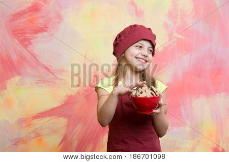 child cooking. small baby girl or cute child with happy face in red chef hat and cooks apron holding bowl with chocolate cookies on colorful abstract background cooking food copy space