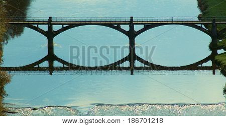Bridge reflecting in blue waterway in the Ardennes