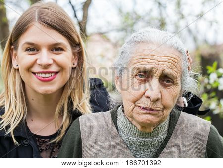 Portrait of a sick elderly woman with her young carer in the park
