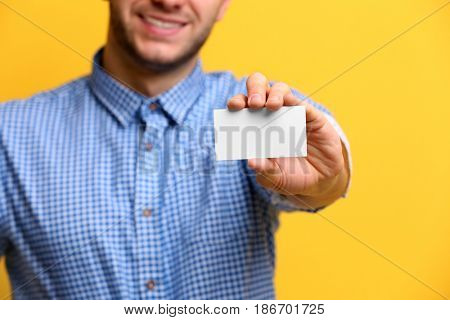 Young man with business card on color background, closeup