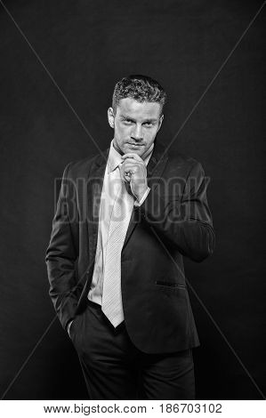 Handsome confident man businessman ceo boss or executive manager posing in formal elegant classy suit with tie on dark background. Business and success black and white