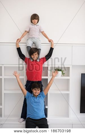 happy young boys having fun and posing line up piggyback in new modern home