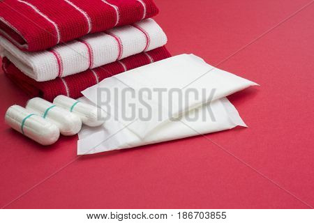 Woman critical days gynecological menstruation cycle blood period. Terry bath red and white towels and menstruation sanitary soft cotton tampons and pads. Woman hygiene protection