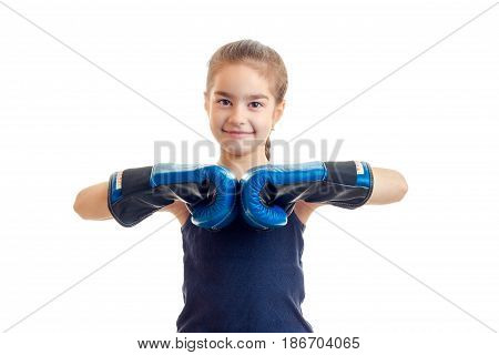 a beaming little baby-girl standing in front of the camera in boxing gloves is isolated on a white background