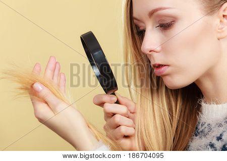 Sad Woman Looking At Damaged Hair Ends.