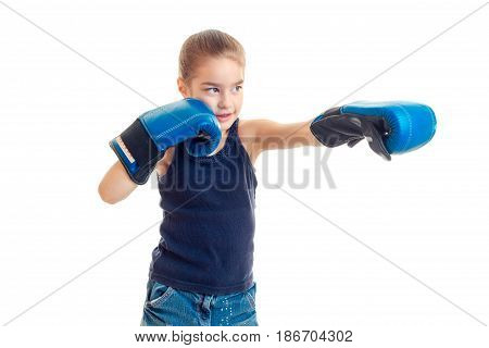 little girl standing in front of the camera in boxing gloves and looks toward isolated on white background