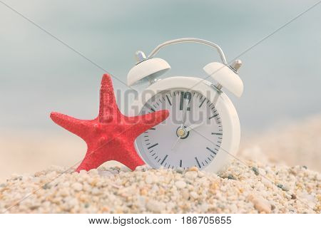 Alarm clock and starfish on sandy beach. Travel and summer vacation concepts