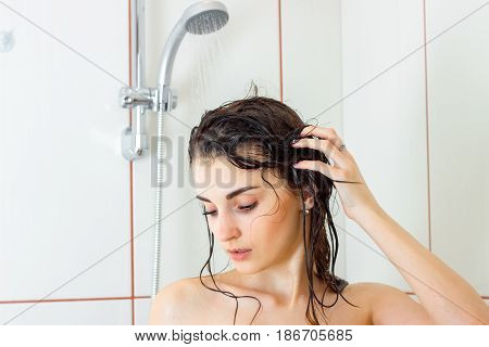 a charming young girl with wet hair lowered her eyes and cleaned in the shower closeup