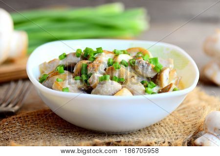 Fried mushrooms slices with sour cream and fresh green onions in a bowl. Healthy vegan meal. Home mushrooms recipe. Fresh mushrooms, green onions, burlap textile on vintage wooden table