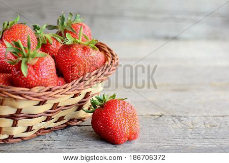 Fresh strawberries. Ripe juicy strawberries in a wicker basket and on a vintage wooden table. Natural source of vitamins and minerals. Closeup