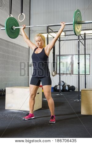 Full length of determined young female athlete lifting weights in health club