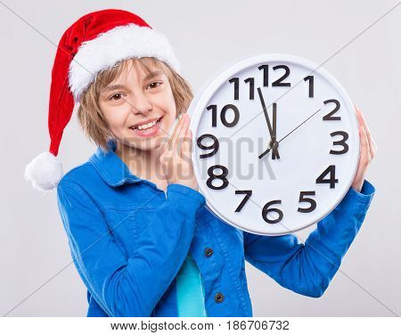 Emotional portrait of attractive caucasian little girl wearing Santa Claus red hat. Funny cute smiling child 10 year old with big clock on gray background. Winter holiday christmas concept.