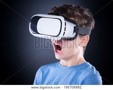 Amazed teen boy screaming, wearing virtual reality goggles watching movies or playing video games. Surprised teenager looking in VR glasses and shouting out loud.