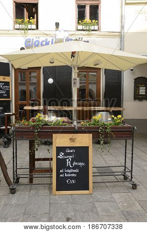 GRAZ, AUSTRIA - MARCH 19, 2017: Wooden flowerpot stand at the entrance of a resturant on Glockenspielplatz square in Graz the capital of federal state of Styria Austria.