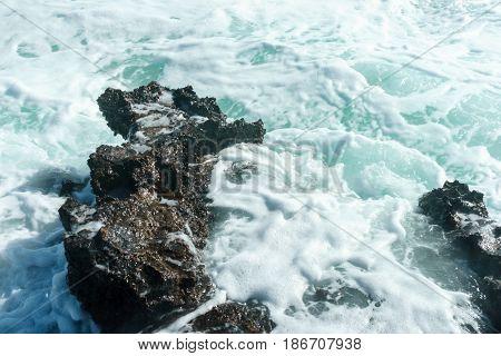 Sea foam and rocky coast, close up
