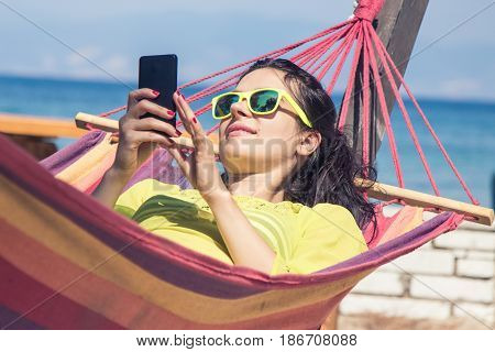 Young Happy Woman Relaxing In Hammock Using Mobile Phone at the seaside